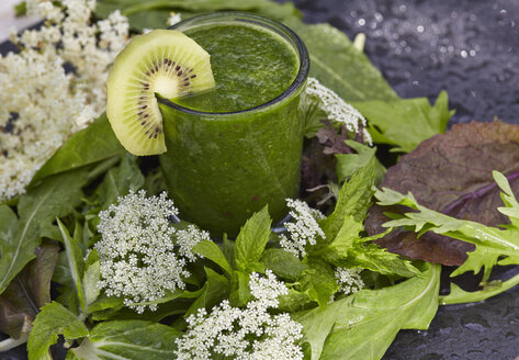Glass of green smoothie decorated with kiwi slice, leaves and blossoms - AKF000406