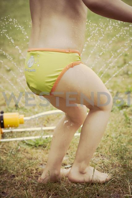Lttle girl having fun with lawn sprinkler in the garten, partial view - LVF001576
