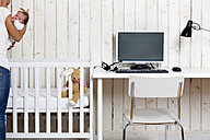 Woman at home office with her baby - DRF000938