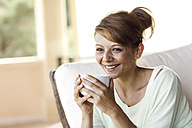 Smiling brunette woman holding cup - GDF000346