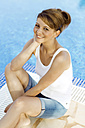Smiling brunette woman at the swimming pool - GDF000354