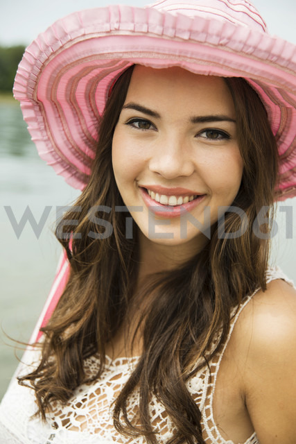 Portrait of smiling young woman on the beach wearing pink summer hat - UUF001203