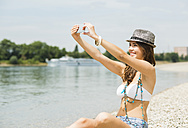 Portrait of young woman taking a selfie with her smartphone on the beach - UUF001228