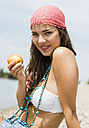 Portrait of young woman with apple on the beach - UUF001282
