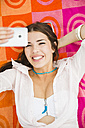 Portrait of young laughing woman lying on beach towel taking a selfie, elevated view - UUF001291