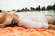 Young woman wearing summer hat relaxing on beach towel - UUF001274