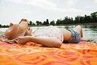 Young woman wearing summer hat relaxing on beach towel - UUF001275