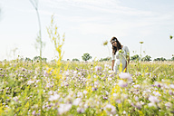 Portrait of young woman standing on flower meadow - UUF001240