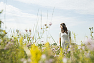 Portrait of young woman standing on flower meadow - UUF001244