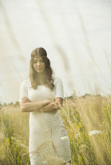Portrait of young woman with crossed arms standing on flower meadow - UUF001253