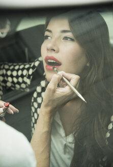 Female visagiste applying lipstick on young woman's lips - UUF001326