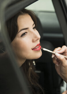 Female visagiste applying lipstick on young woman's lips - UUF001329