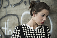 Portrait of pensive young woman with red lips in front of wall with graffiti - UUF001334