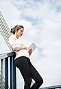 Young woman leaning on railing using digital tablet - UUF001350
