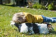 Boy playing with Jack Russel Terrier puppy in garden - MJF001312