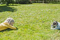 Boy playing with Jack Russel Terrier puppy in garden - MJF001313
