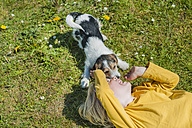 Boy playing with Jack Russel Terrier puppy in garden - MJF001318
