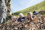 Three playful children in autumn leaf heap - HHF004837