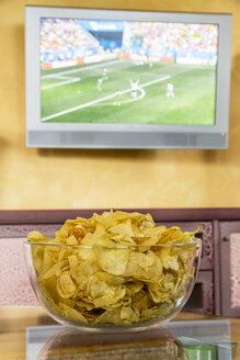 Glass bowl of potato chips in front of flatscreen TV broadcasting a soccer match - EJWF000413