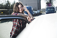 Young woman at car on cell phone - FEXF000098