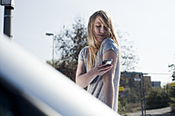 Blond young woman with cell phone outdoors - FEXF000100