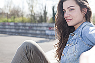Relaxed young woman sitting outdoors - FEXF000117