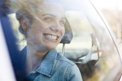 Smiling young woman on back seat of a car - FEXF000121