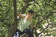 Portrait of little girl climbing on tree - LVF001591
