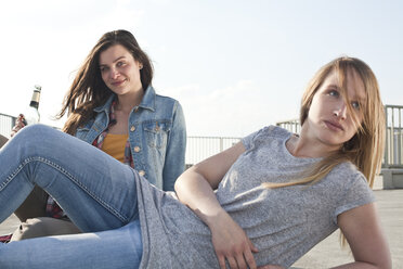 Germany, North Rhine-Westphalia, Cologne, two young women relaxing on parking level - FEXF000137