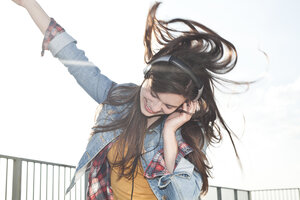 Portrait of happy young woman listening music with headphones - FEXF000140