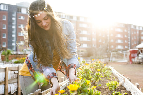 Portrait of young woman at raised bed in front of multi-family house - FEXF000144