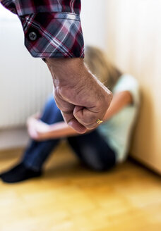 Man's fist in front of a young woman crouching afraid on the floor - EJW000443