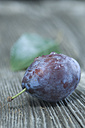 Plums, Prunus domestica subsp. domestica, with water drops on grey wood - ASF005440