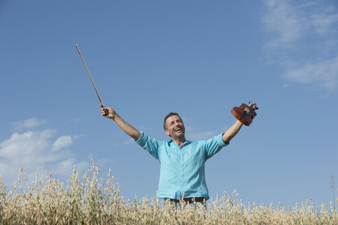 Germany, Bavaria, Starnberg Region, Man playing violin in field - CRF002599