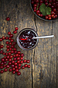 Jam jar of currant jelly, bowl and red currants, Ribes rubrum, on wooden table, elevated view - LVF001602