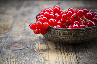 Bowl of red currants, Ribes rubrum, on dark wooden table, partial view - LVF001609