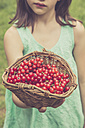 Little girl holding basket of red currants, partial view - LVF001622
