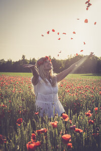 Woman jumping in a poppy field throwing petals in the air - SARF000718