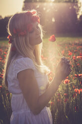 Woman standing in a poppy field at back light - SARF000737