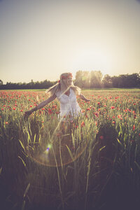 Woman dancing in a poppy field at back light - SARF000738