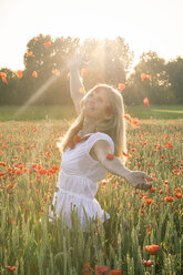 Woman standing in a poppy field throwing petals into the air - SARF000735