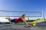 Germany, Young woman playing beach volleyball - STSF000443