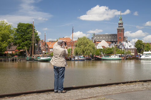 Germany, Lower Saxony, Leer, senior man taking a picture of the city and the museum harbour with his smartphone - WIF000896