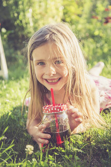 Portrait of smiling little girl lying on a meadow in the garden - SARF000727