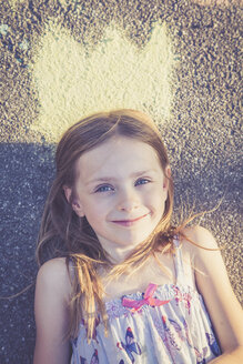 Portrait of smiling little girl lying on tarmac with a painted crown - SARF000730