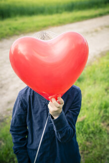 Little boy hiding his face behind a red heart-shaped balloon - SARF000732