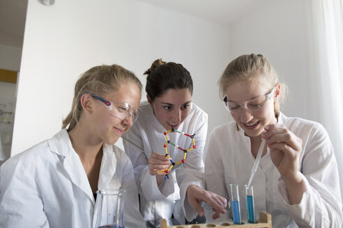 Teenage girls and young woman having a chemical experiment - SGF000825