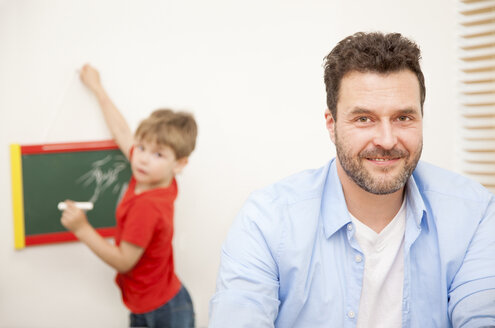 Portrait of smiling father with his little son in the background - MMFF000284