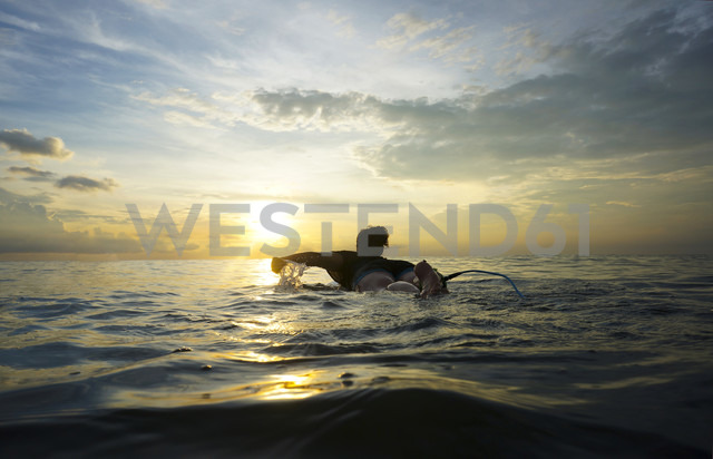 Indonesia, Bali, Canggu, young woman at her surfboard by twilight - FAF000051