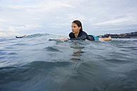 Indonesia, Bali, Canggu, young woman lying on her surf board moving forward - FAF000053
